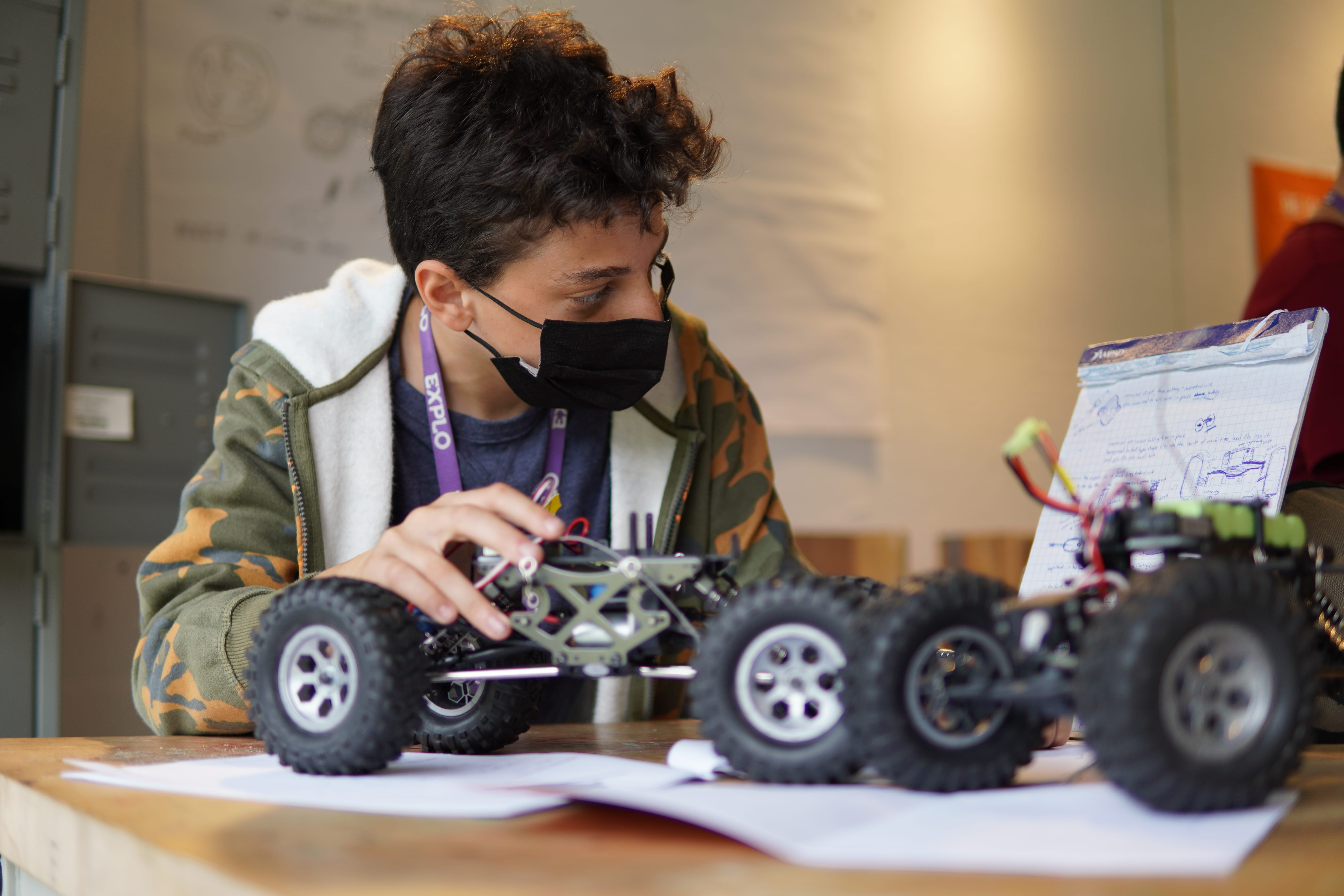 A student in a camo zip up hoodie looks to a reference sheet while constructing an RC car.