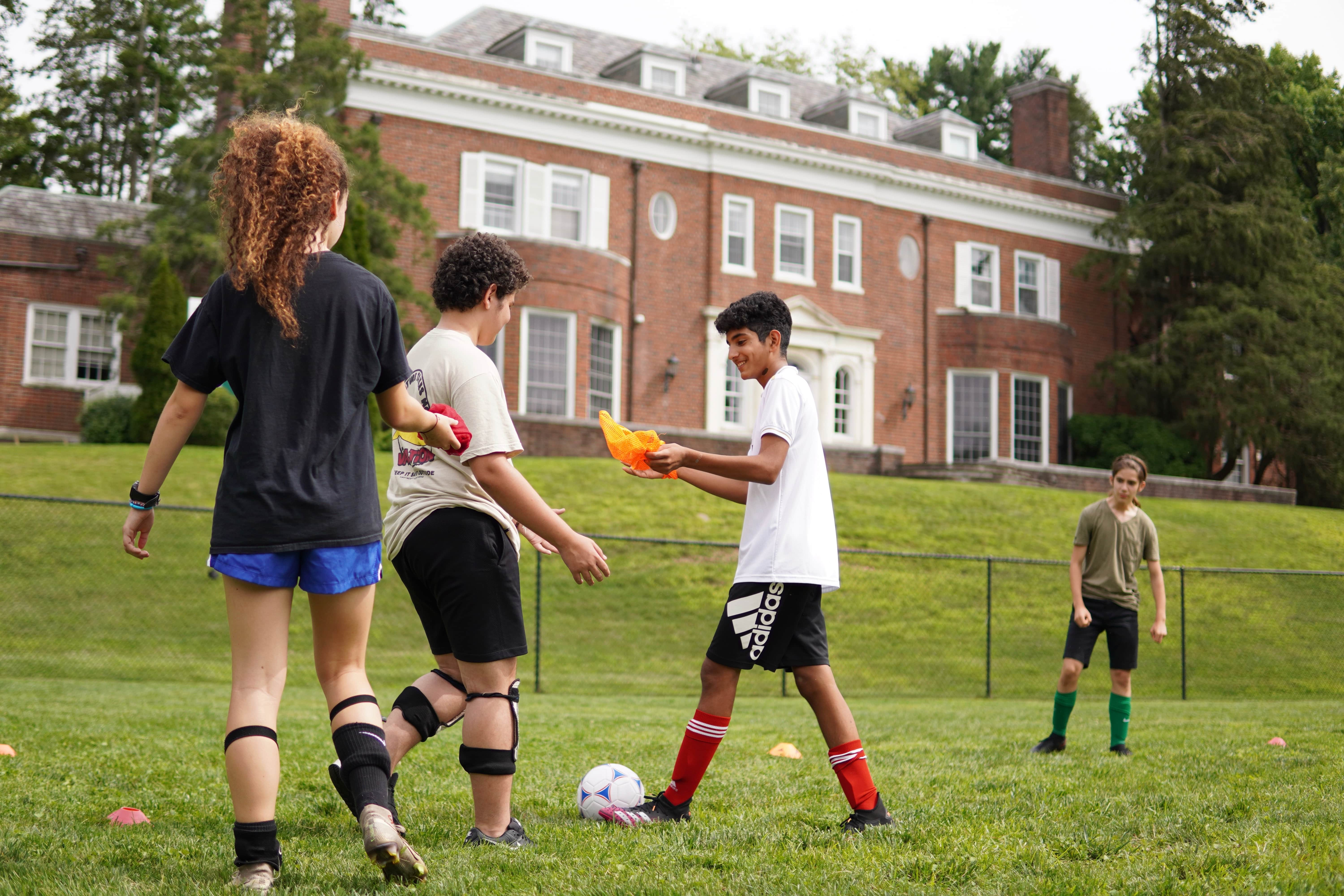 Students gather outdoors on a green field to play soccer. A brick building fills the background behind them.