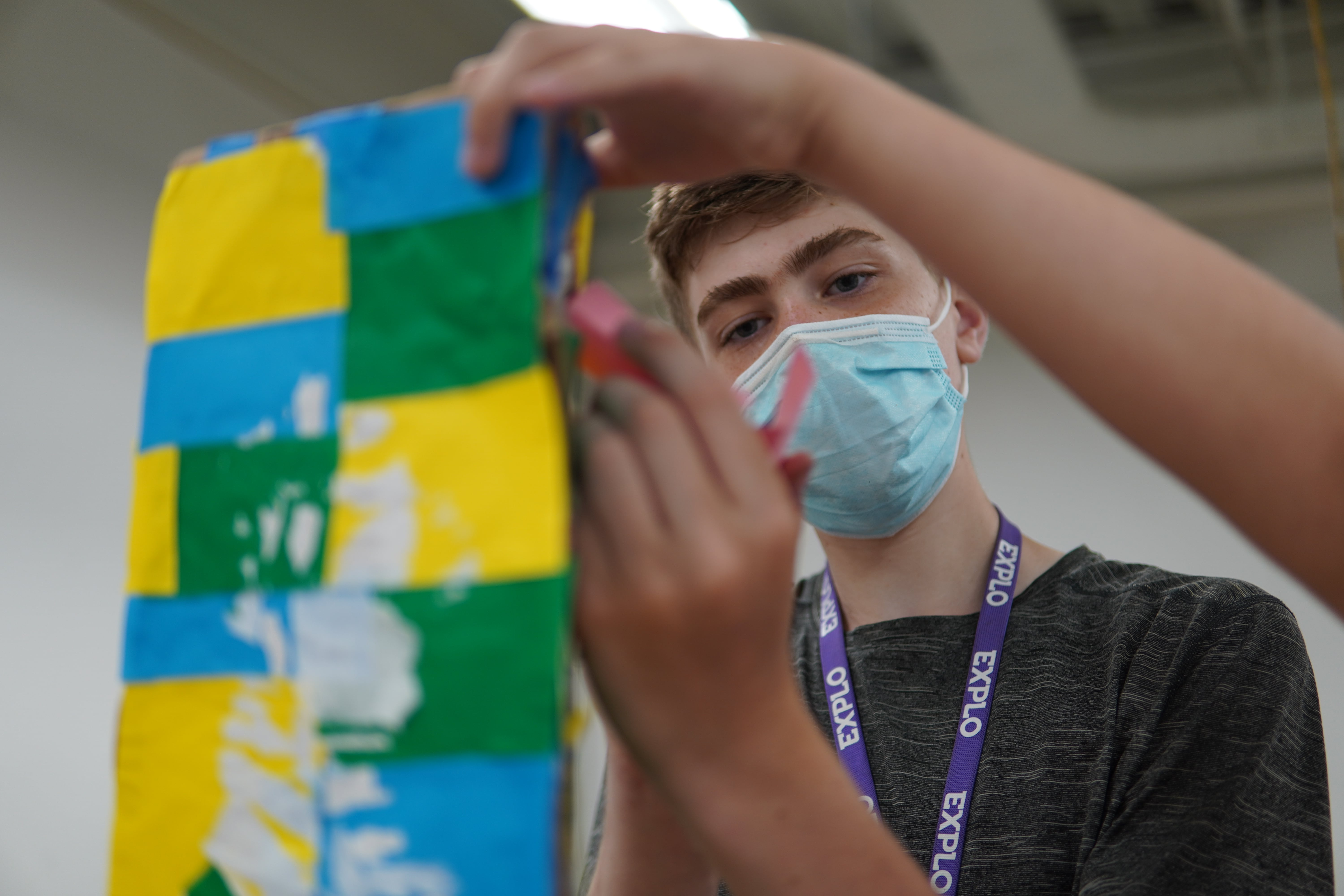 A student in a gray t-shirt focuses on building a papered roller coaster model while the hands of his teammates frame his face.