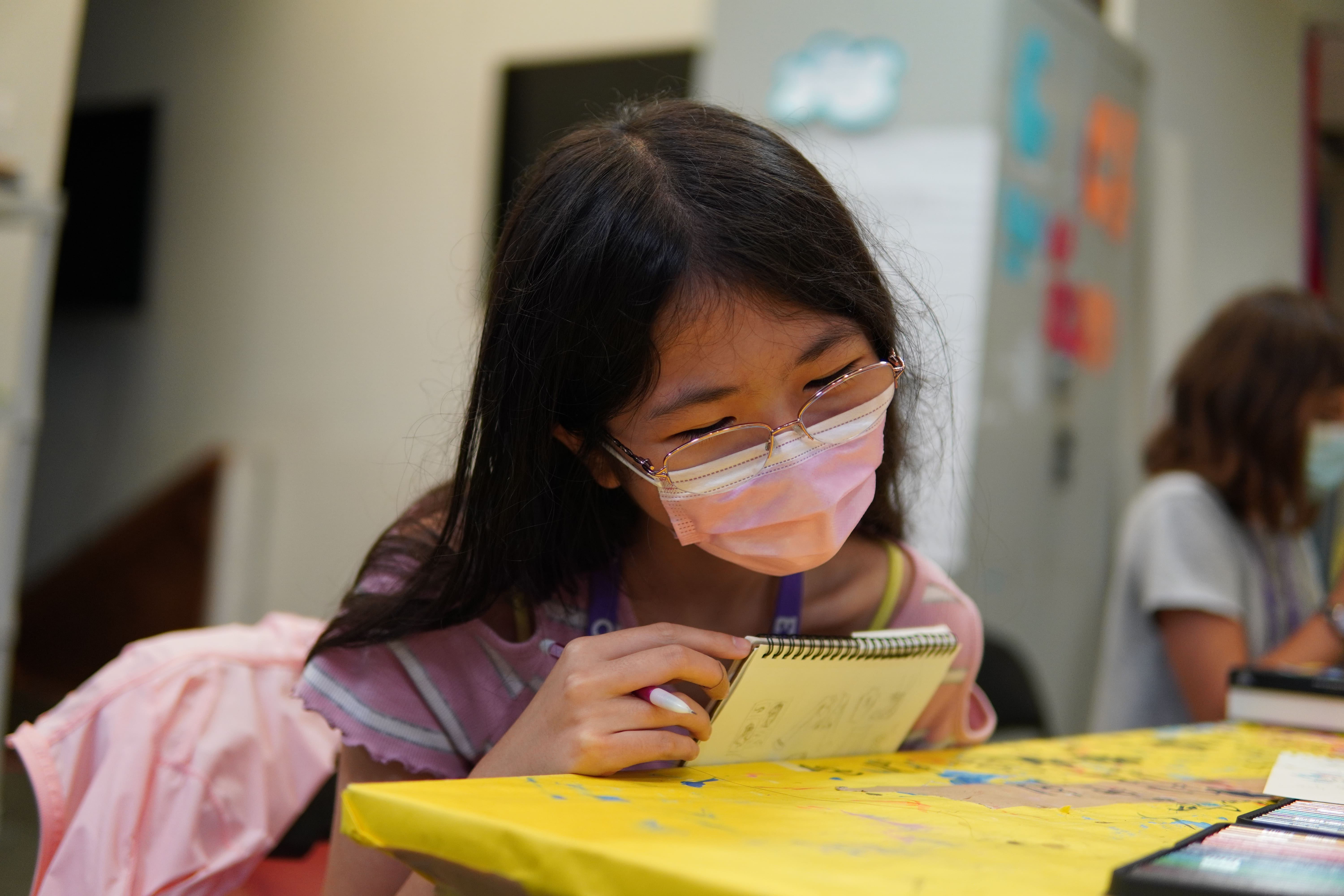 A student in a pink t-shirt and glasses leans forward closer to the yellow table where she sits, engaged in a drawing activity.
