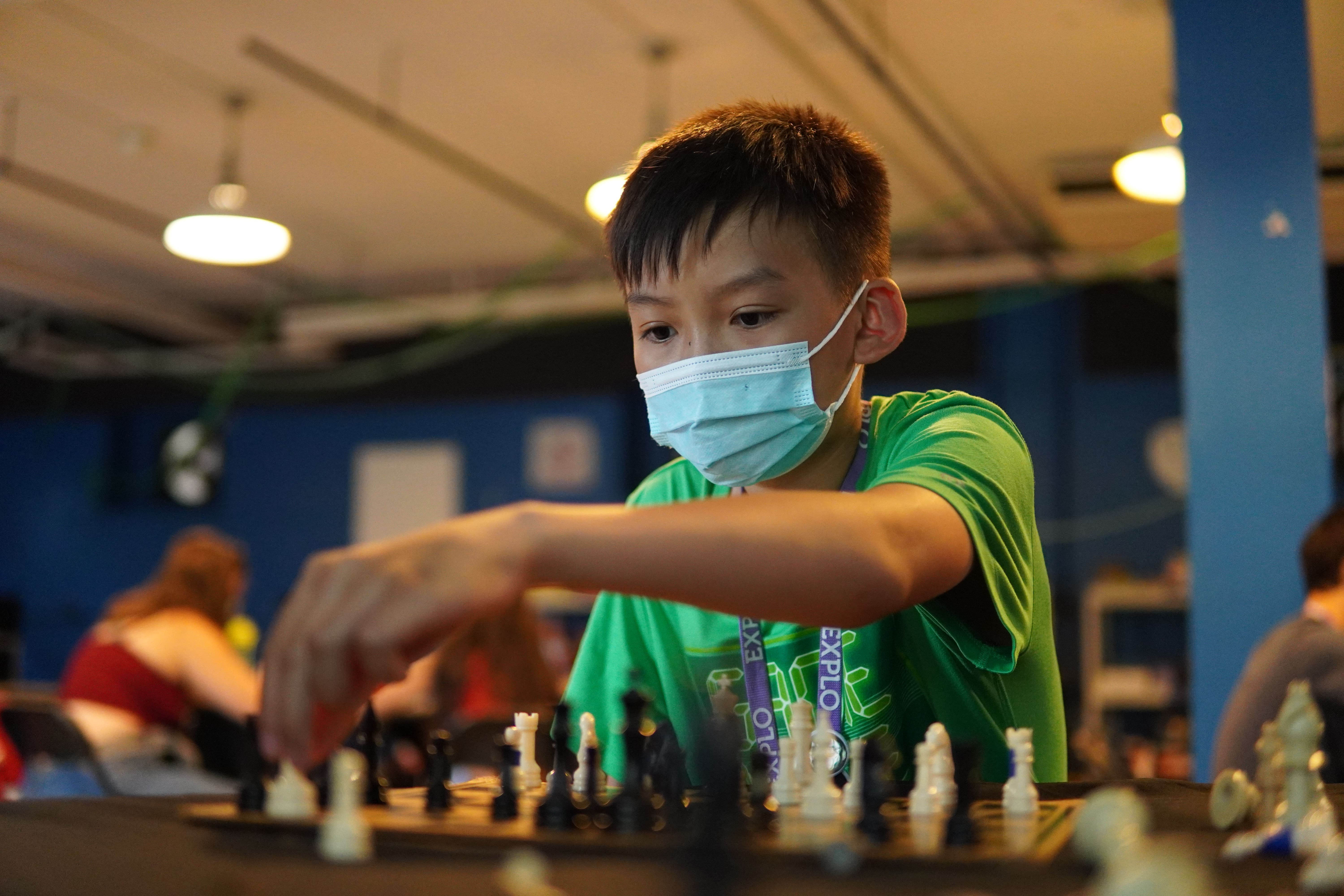 A student in a green shirt moves a chess piece across the board.