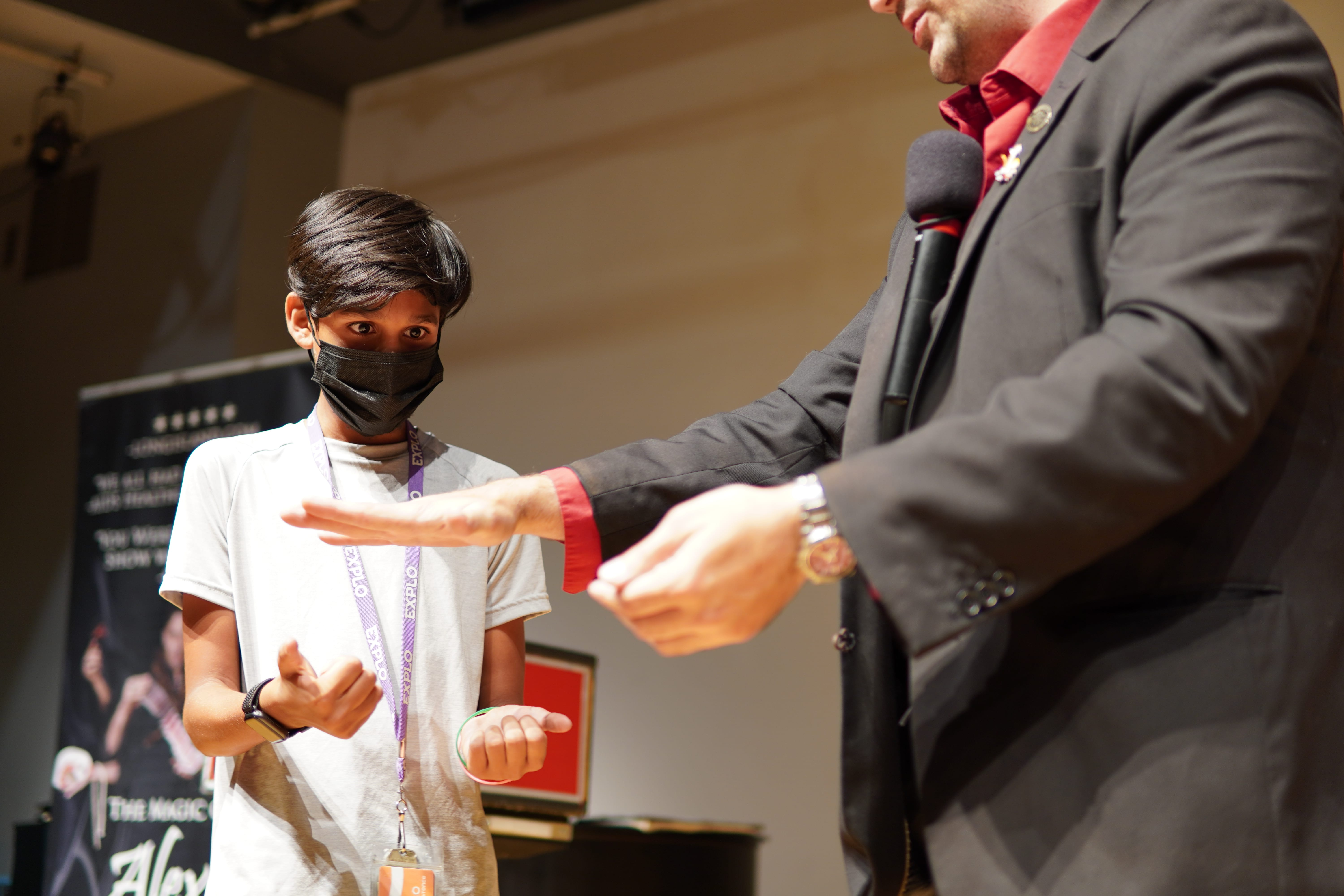 A student in a gray t-shirt holds his hands out while the magician hovers his over the student's to perform a magic trick.