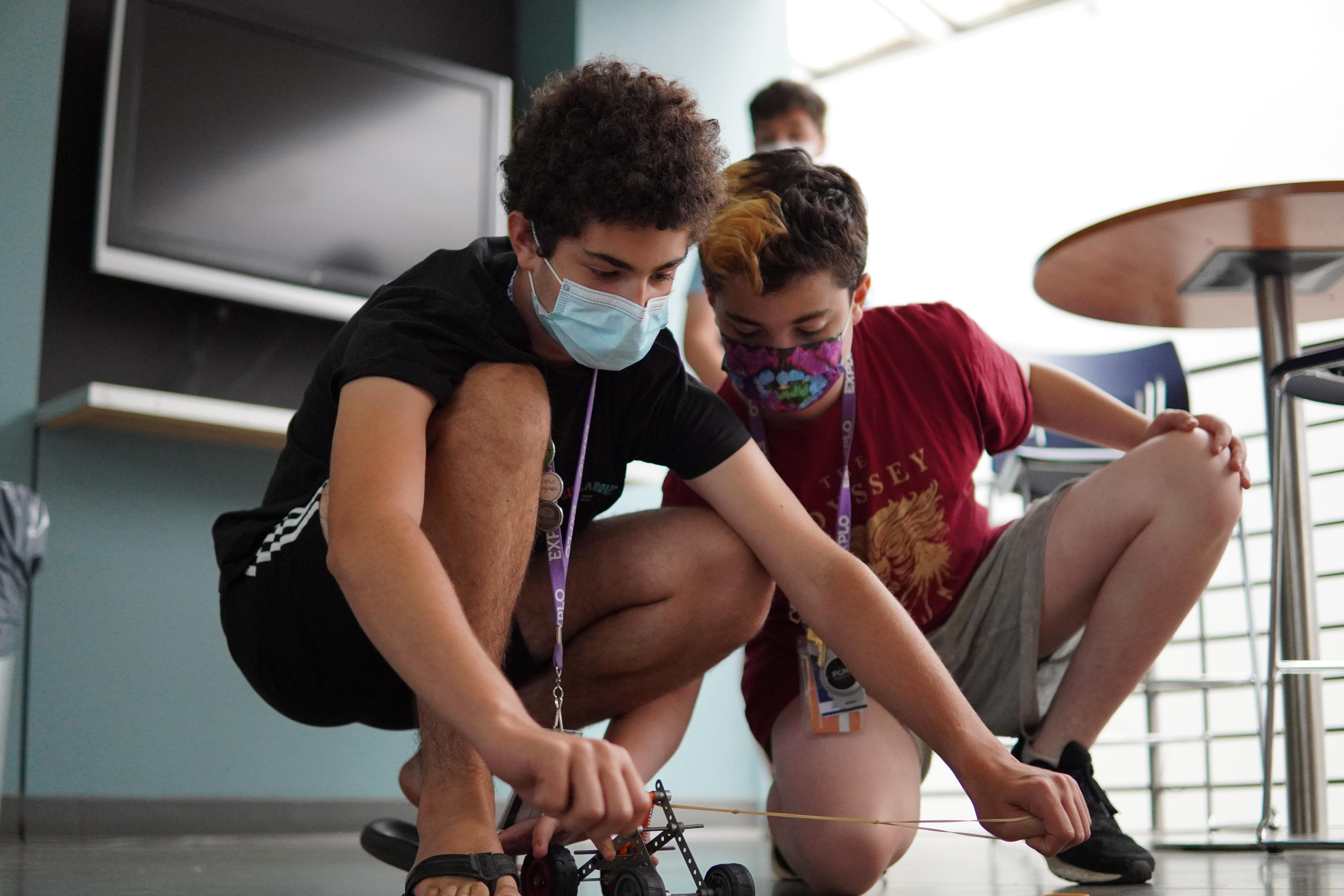 Two students kneel next to the ground to launch an RC car across the floor with a rubber band.