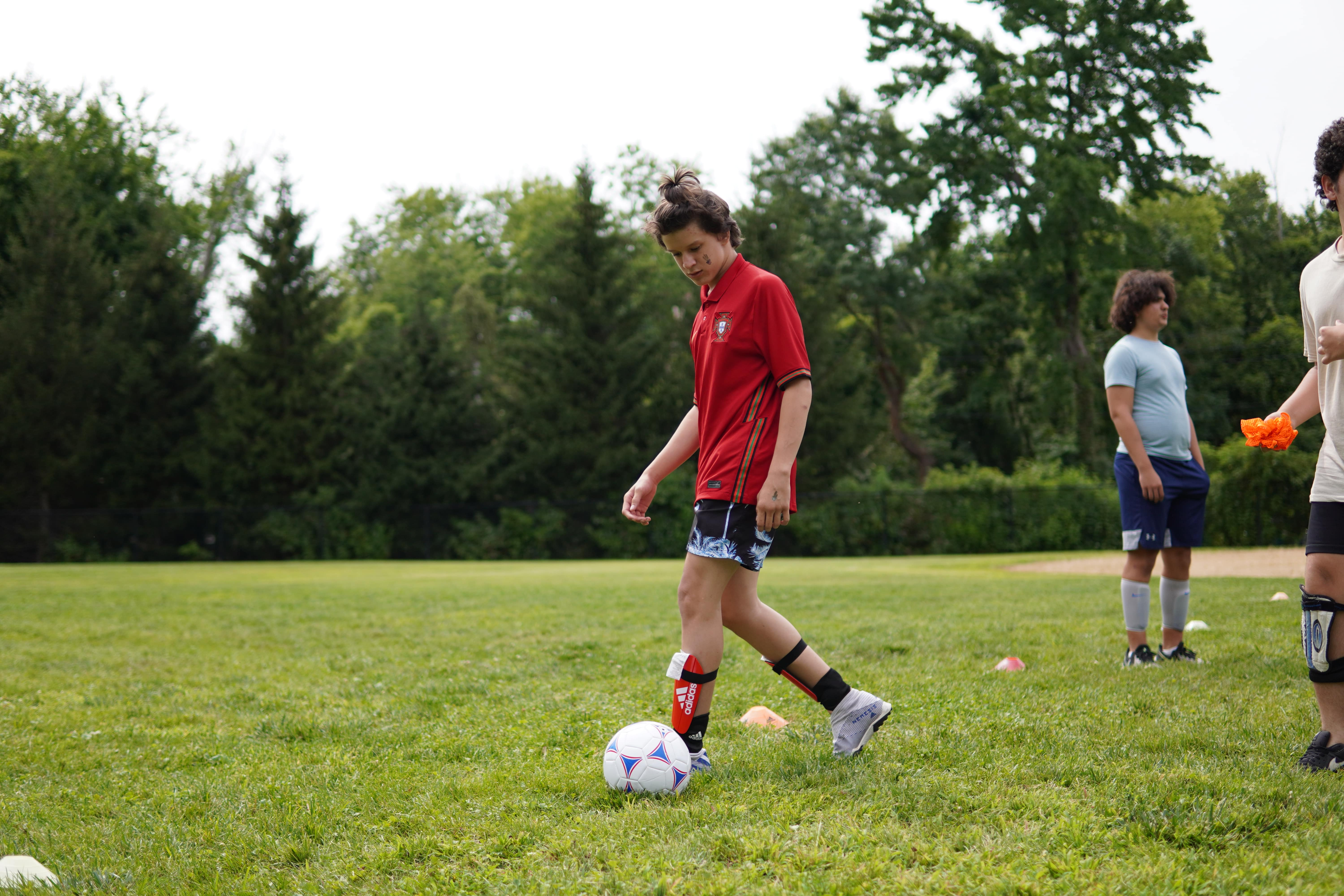 A student in a red soccer jersey stands on a field outdoors walking by the soccer ball preparing to kick it.