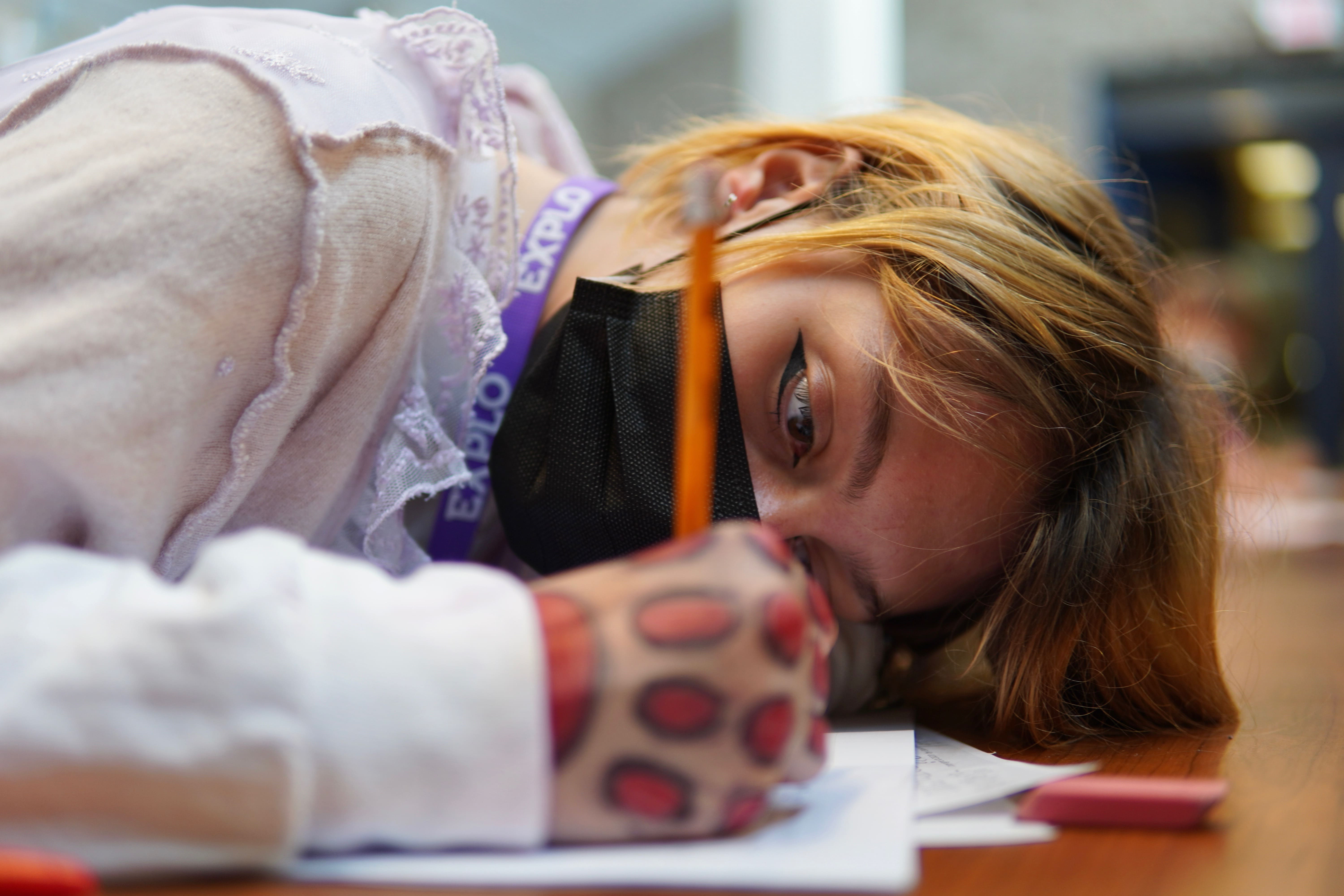 A student with blonde hair lays their head on the table and writes, eyes focused.