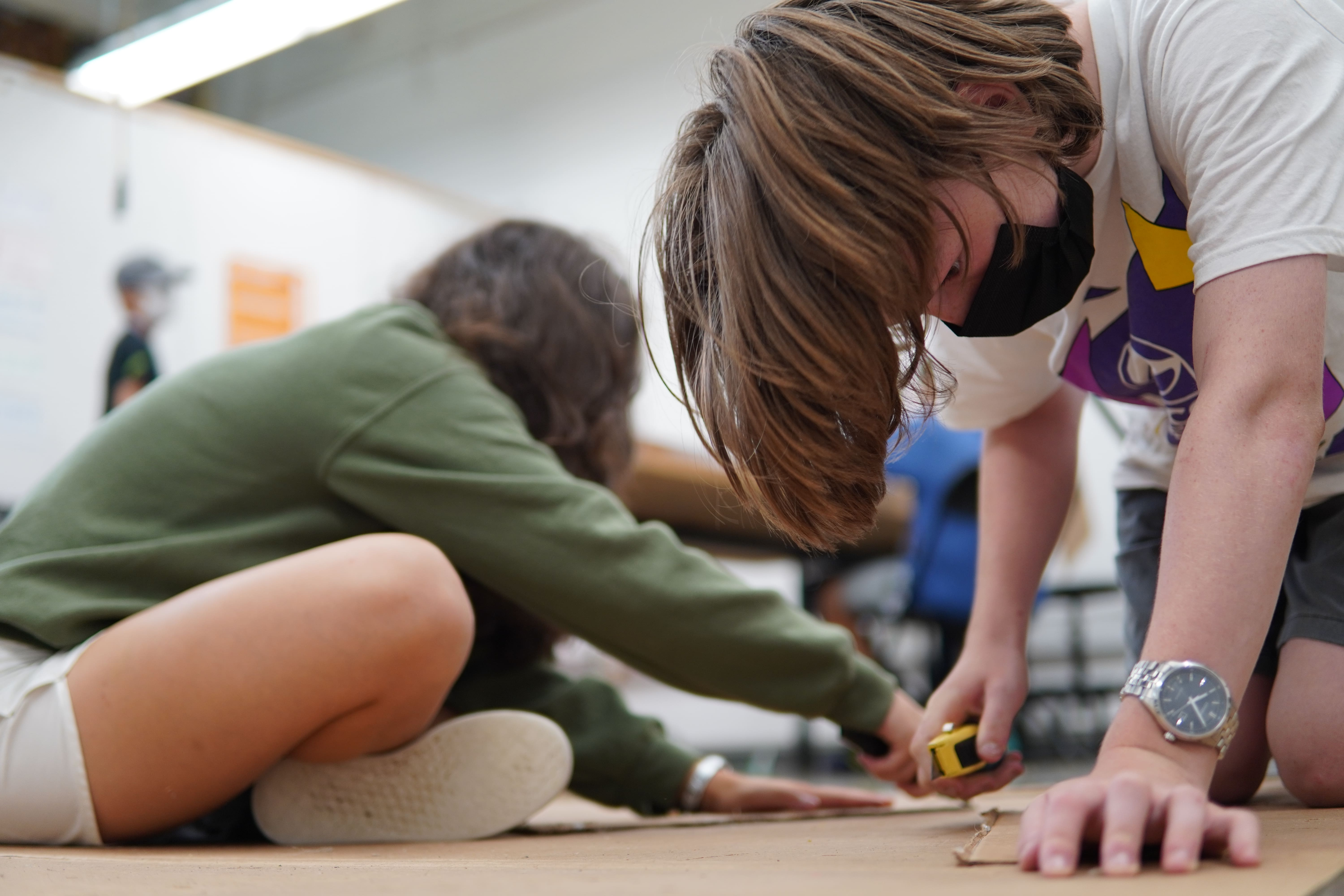 A student in a white t-shirt leans over a piece of cardboard on the floor to cut out a piece of additional cardboard for his roller coaster model.
