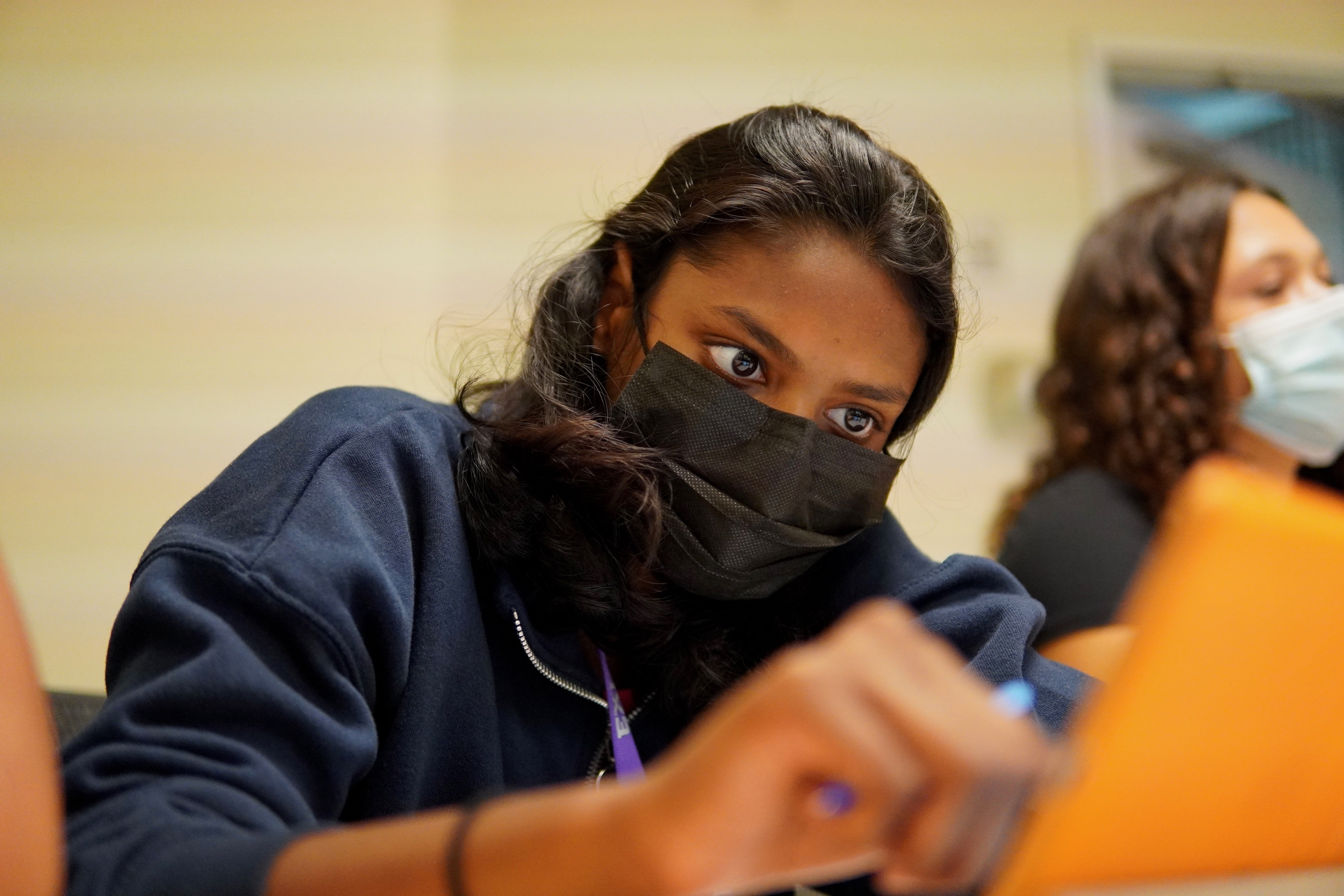 A student in a navy blue hoodie fixates on the iPad in front of her conducting research.