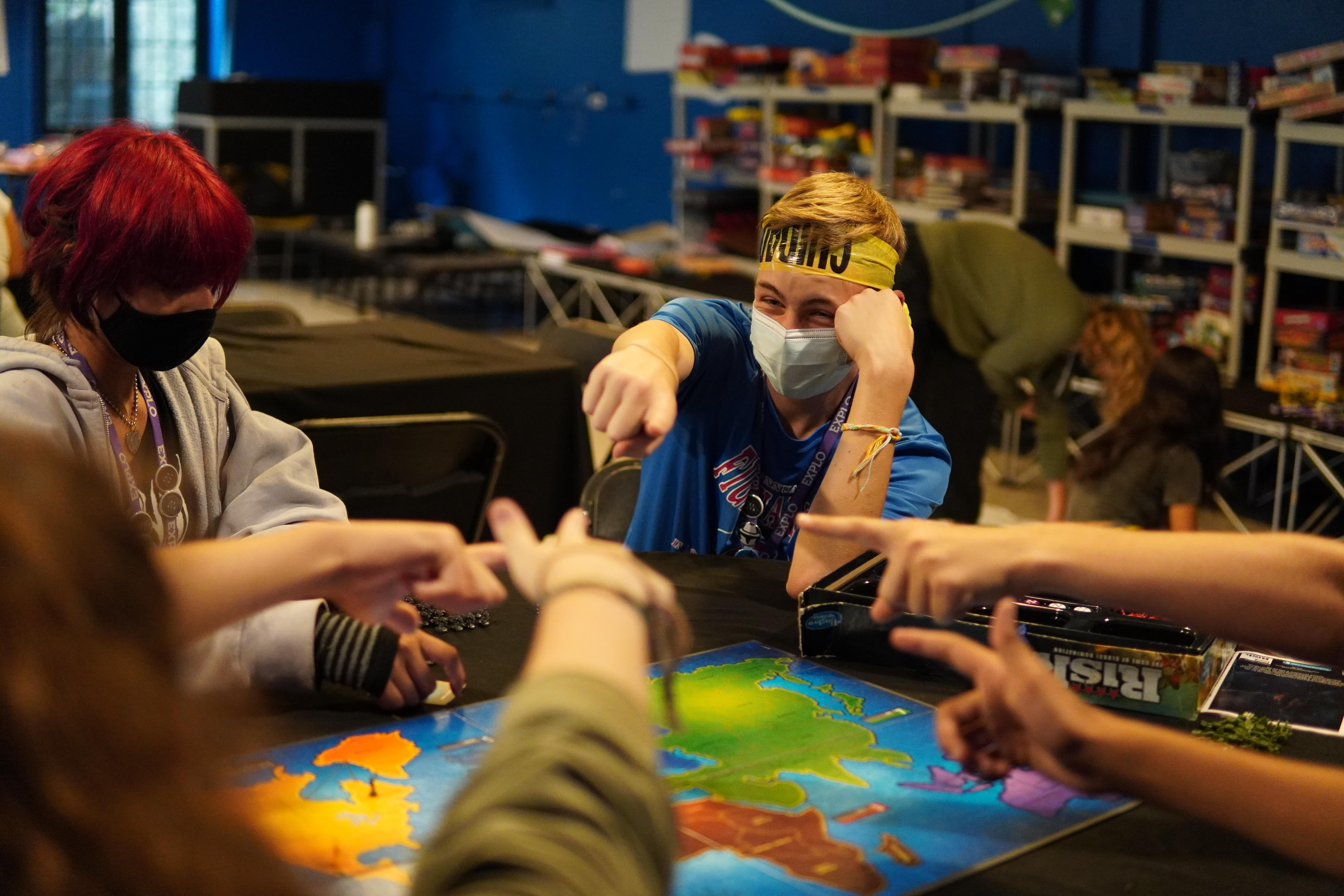 Students sitting at a round table around a game of Risk all point their fingers in the middle of the table at each other.
