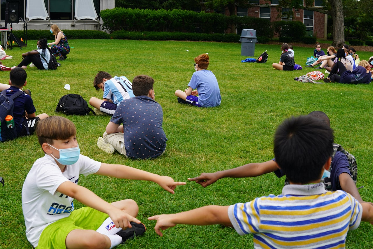 Three friends sitting in a circle on the quad
