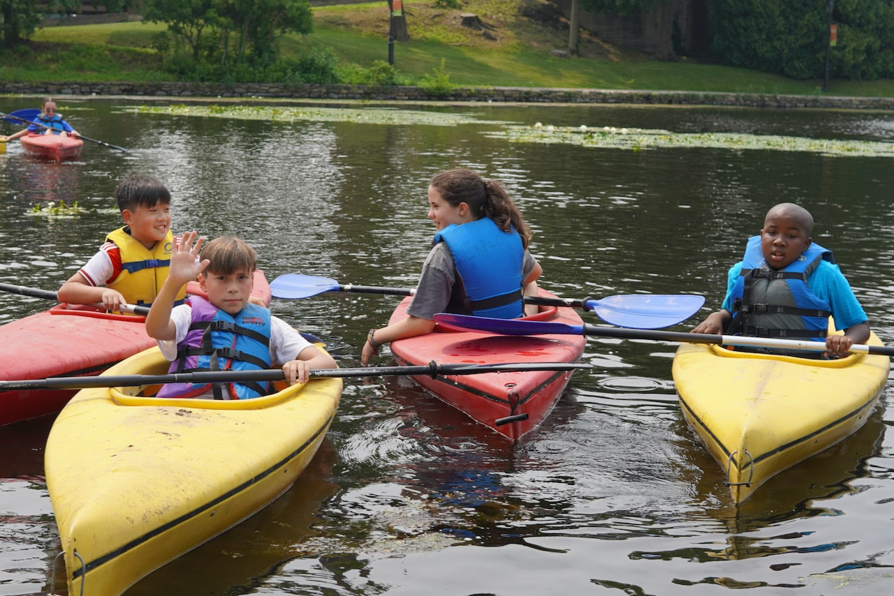 Four students chat while sitting in their red and yellow kayaks