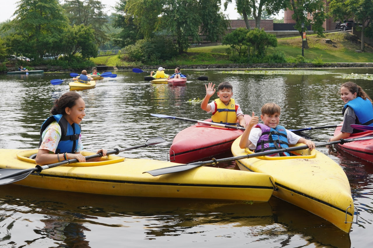 Four students chat while paddling in their red and yellow kayaks