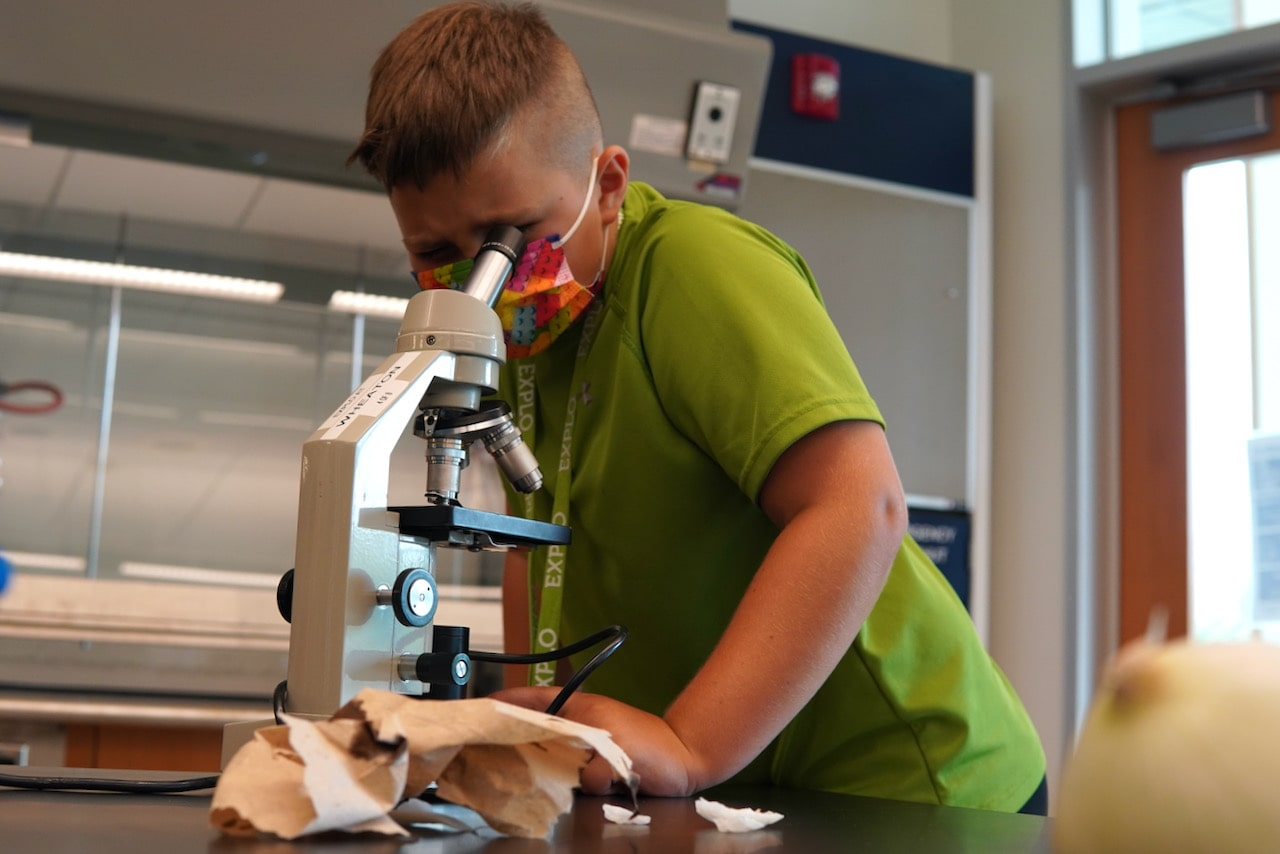 A student leans on the table and looks though a microscope