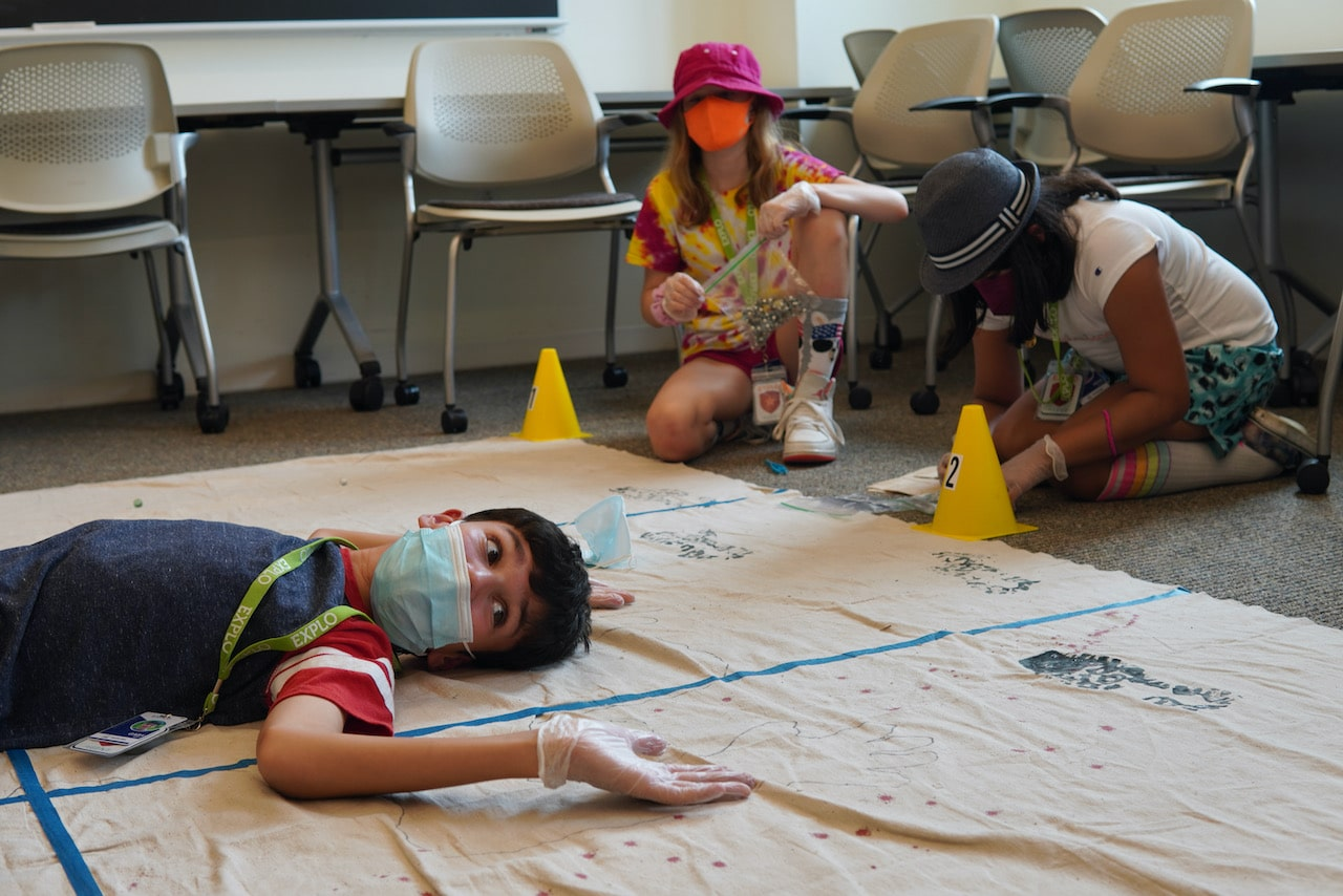 A student lies down on the crime scene canvas as two students take notes in the background