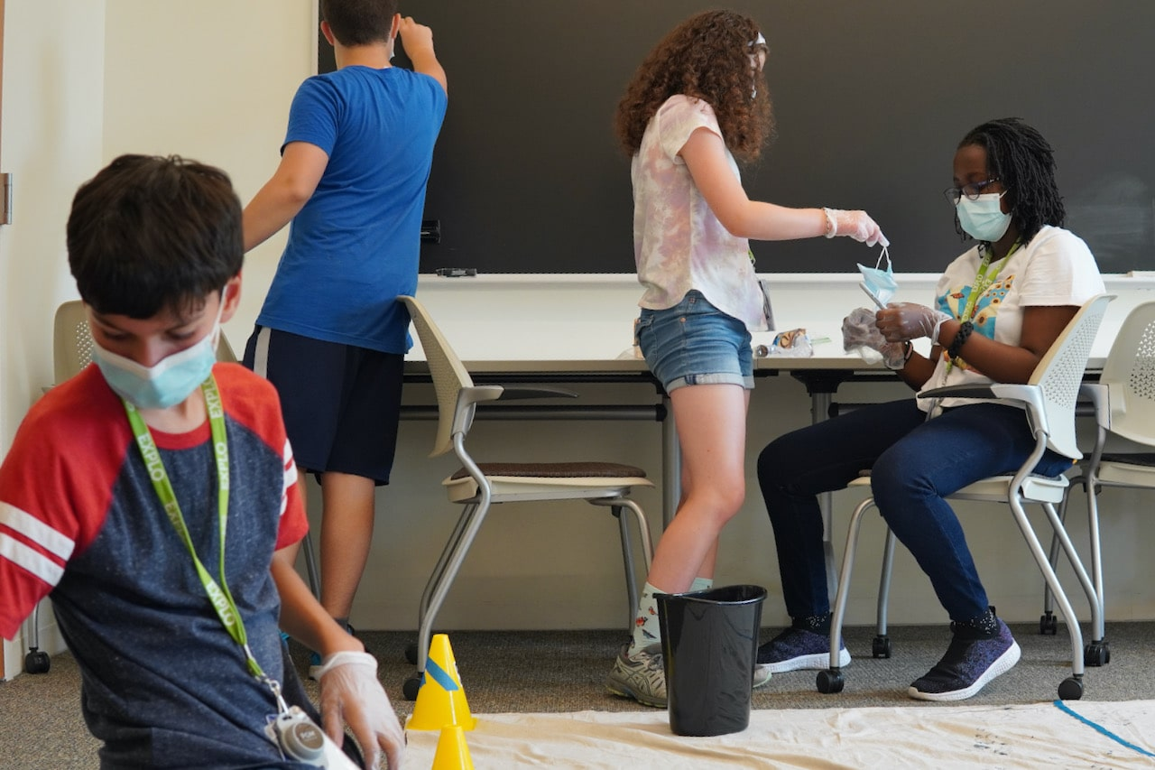 Three students collect evidence from the crime scene while another student writes on the chalkboard