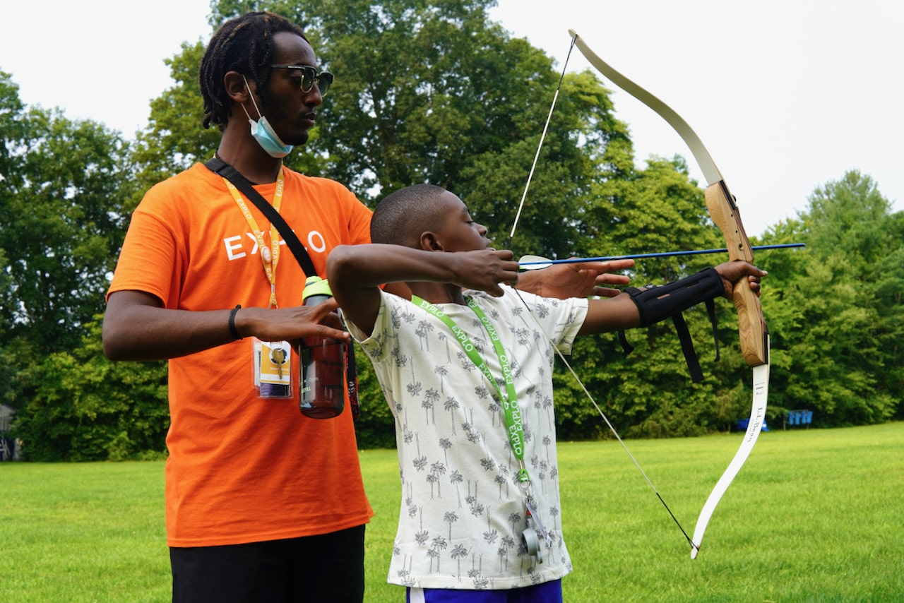 An instructor helps a student with his shooting form