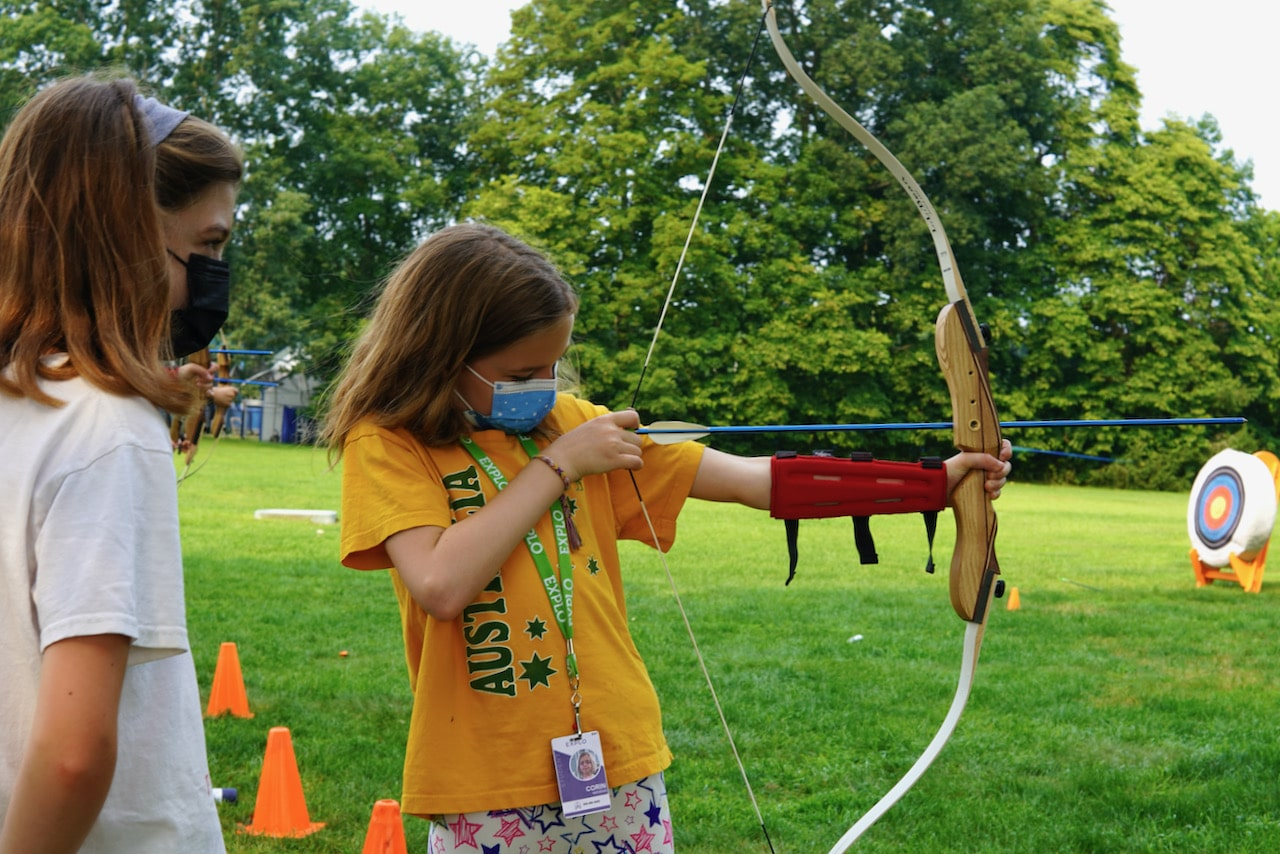 A student aims at the target while her friend looks over her shoulder