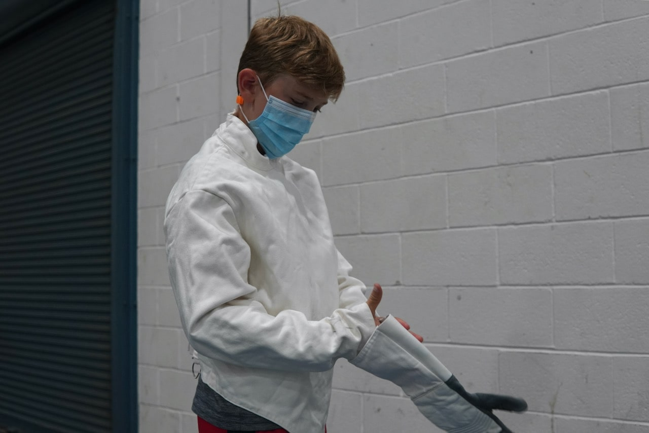 A student puts on his fencing glove