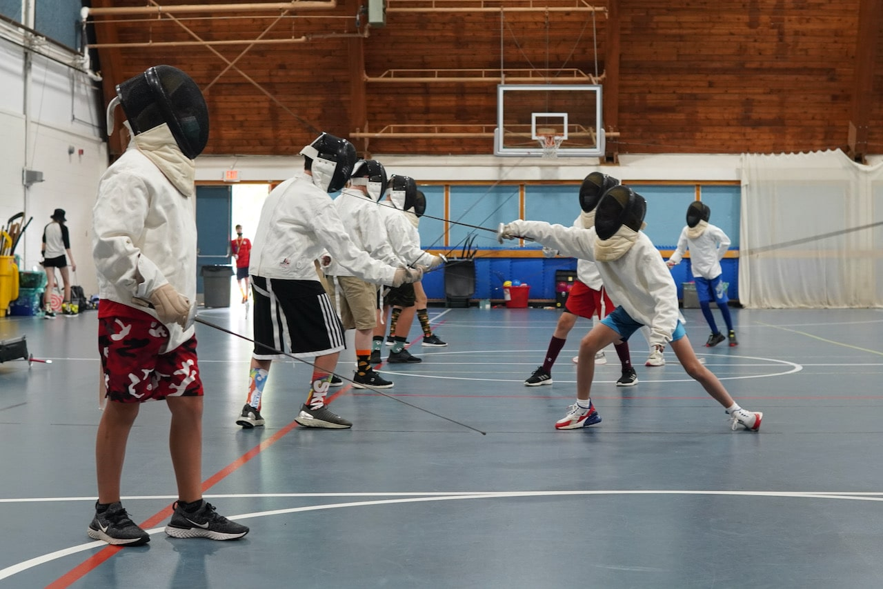 Two lines of students facing each other practicing their lunges and parries
