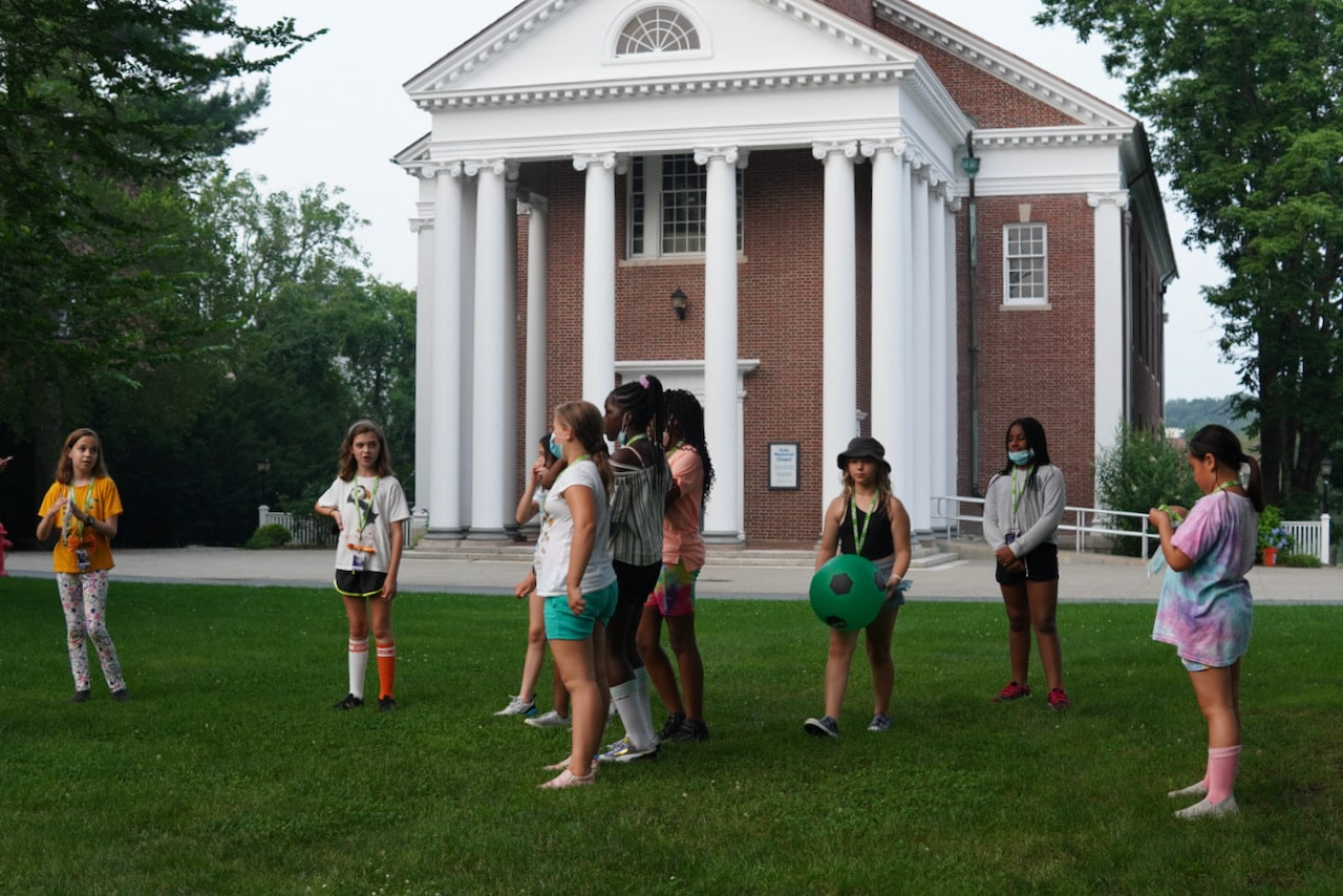 A group of students stand in front of the Wheaton Chapel during the scavenger hunt