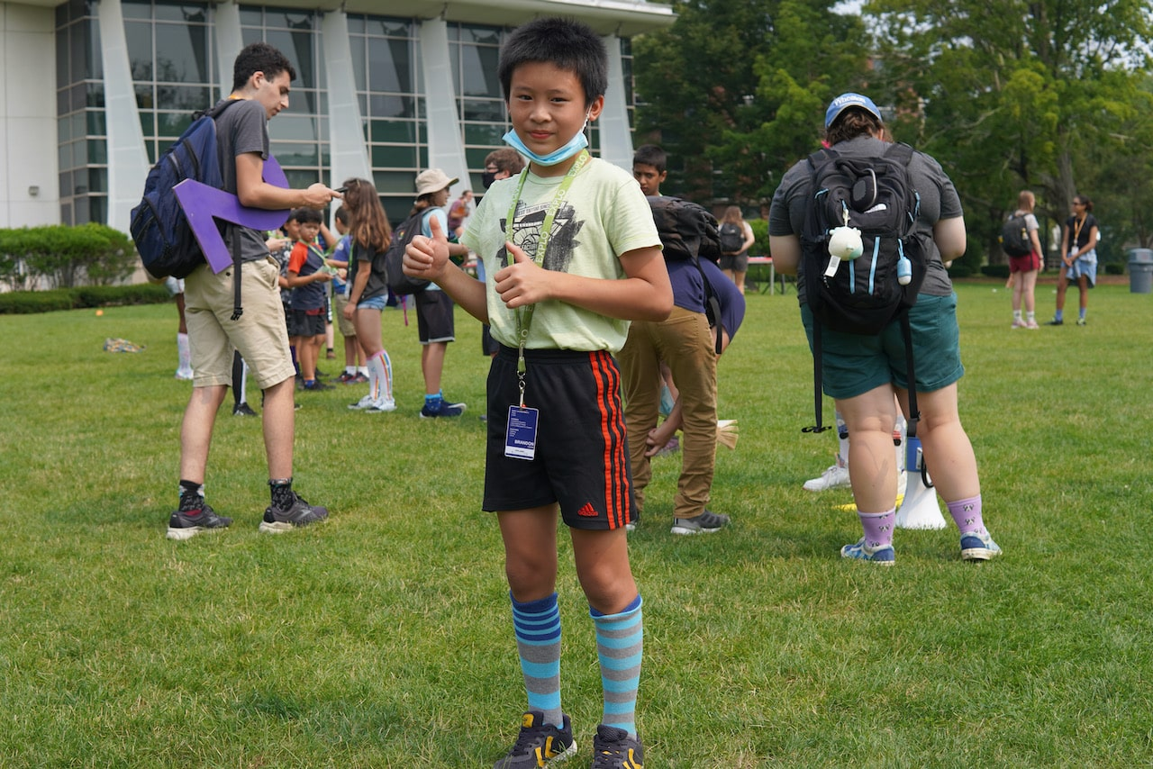 A student poses for a picture in his blue tall socks on the quad