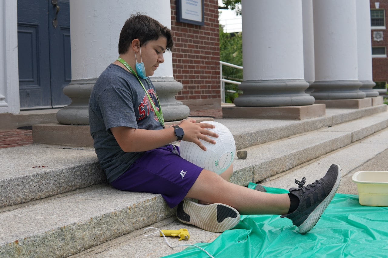 A student sits on the steps of the chapel and decorates his planet