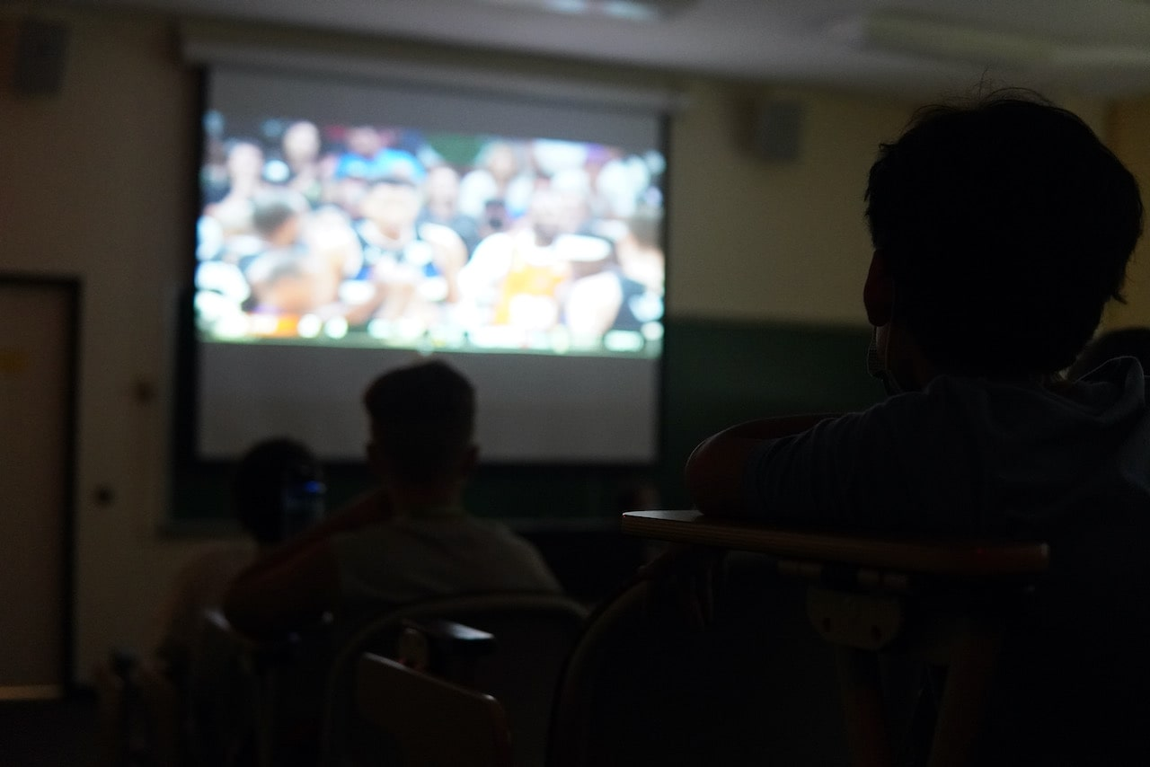 A group of students watching the NBA Finals on the projector screen
