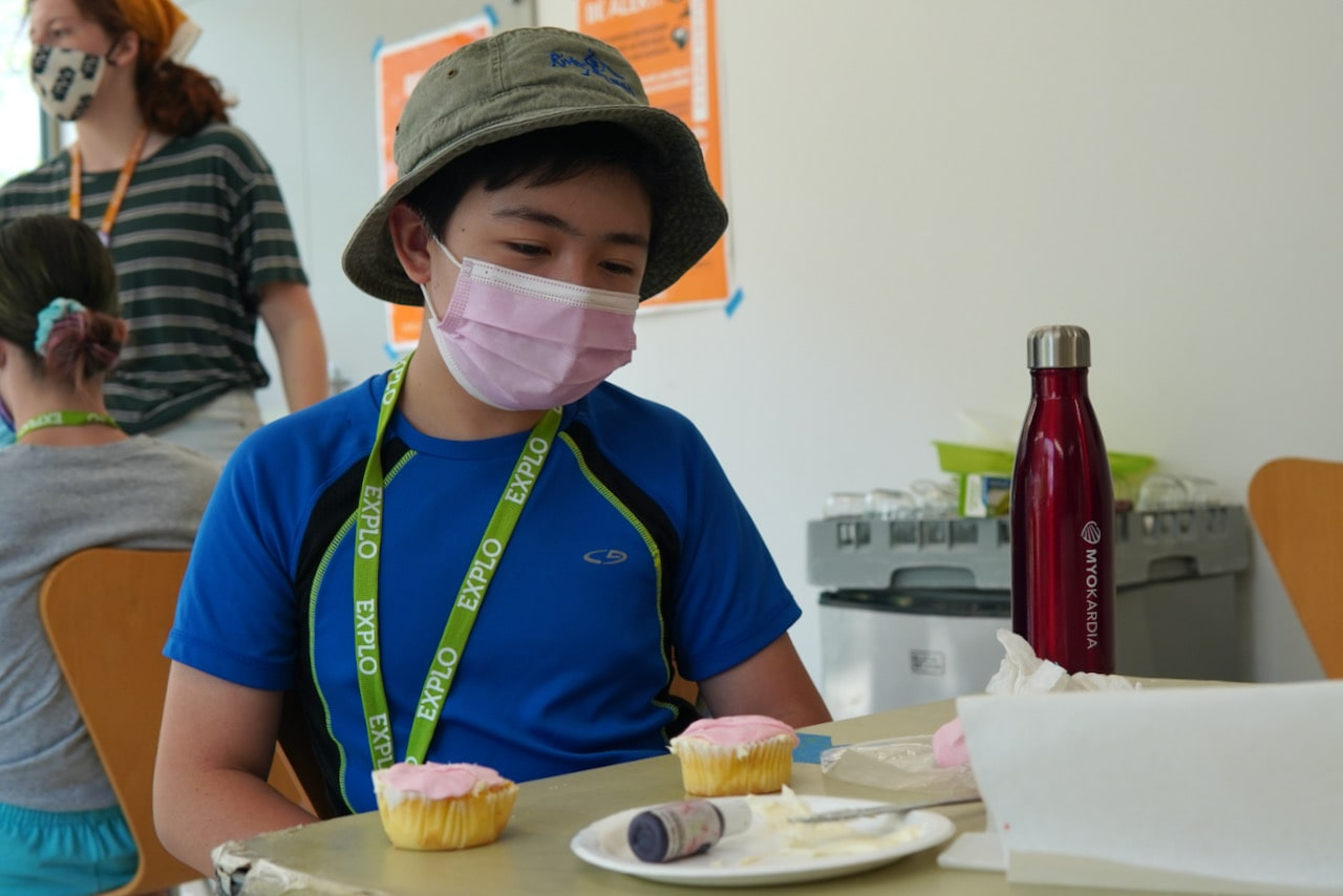 A student smiles while sitting at a table with two pink cupcakes on it