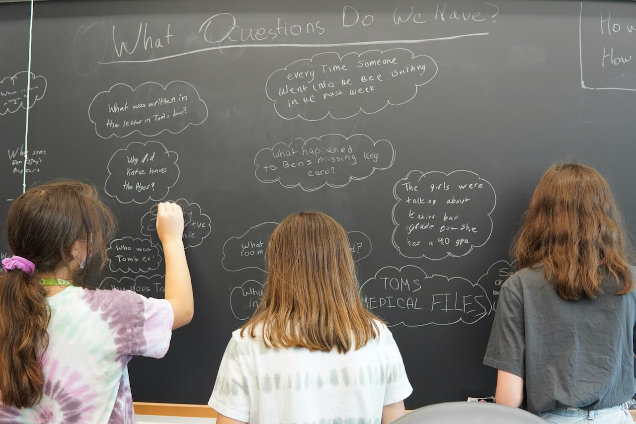 Three students write questions on the chalkboard