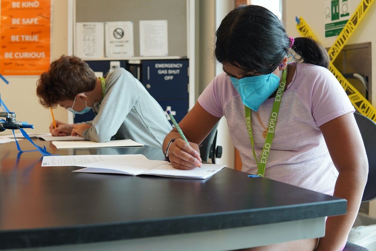 Two students sit next to each other writing down notes