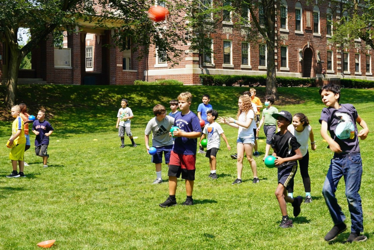 A student throws a red ball at the other side while students run around in the background