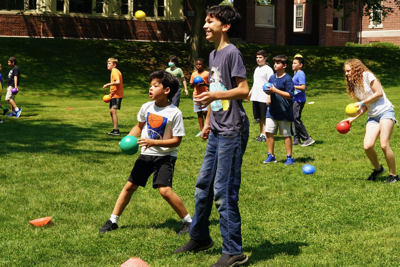 A student smiles while other students prepare to throw balls at the opposing team