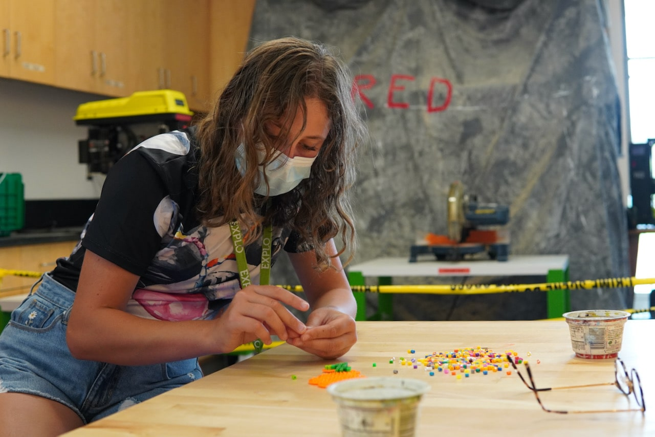 A student leans on the table while placing beads on a template