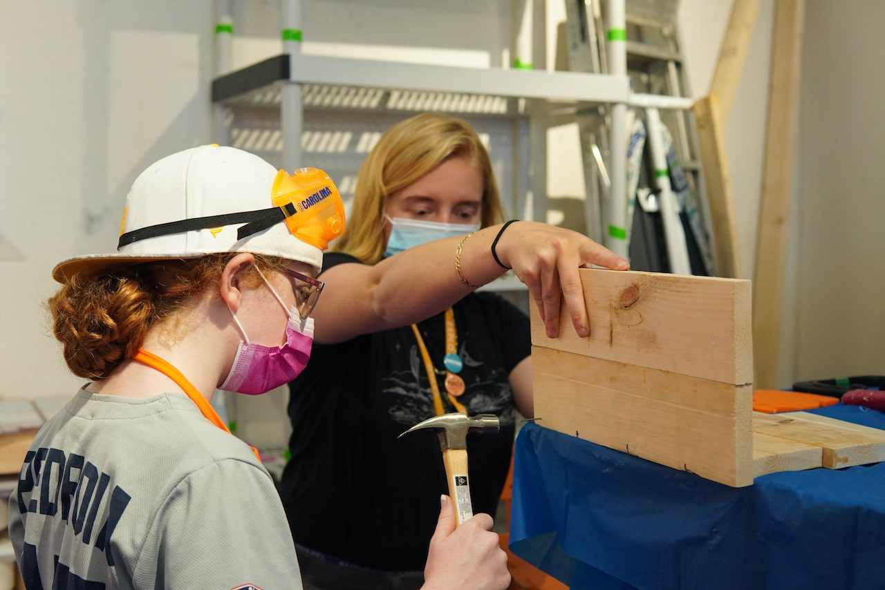 A student hammers a nail while an instructor holds up a piece of wood