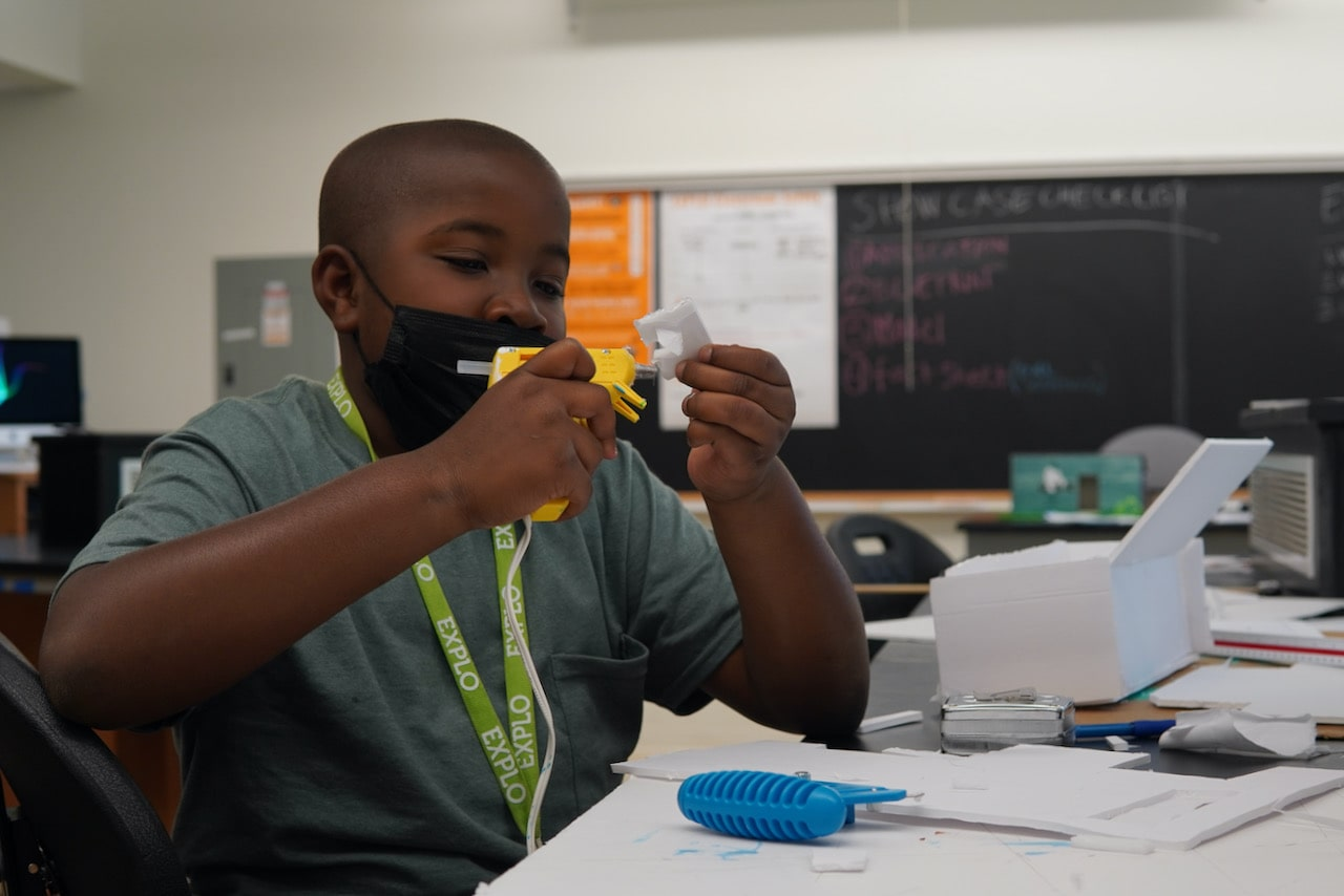 A student concentrates while using a hot glue gun on a piece of foam core