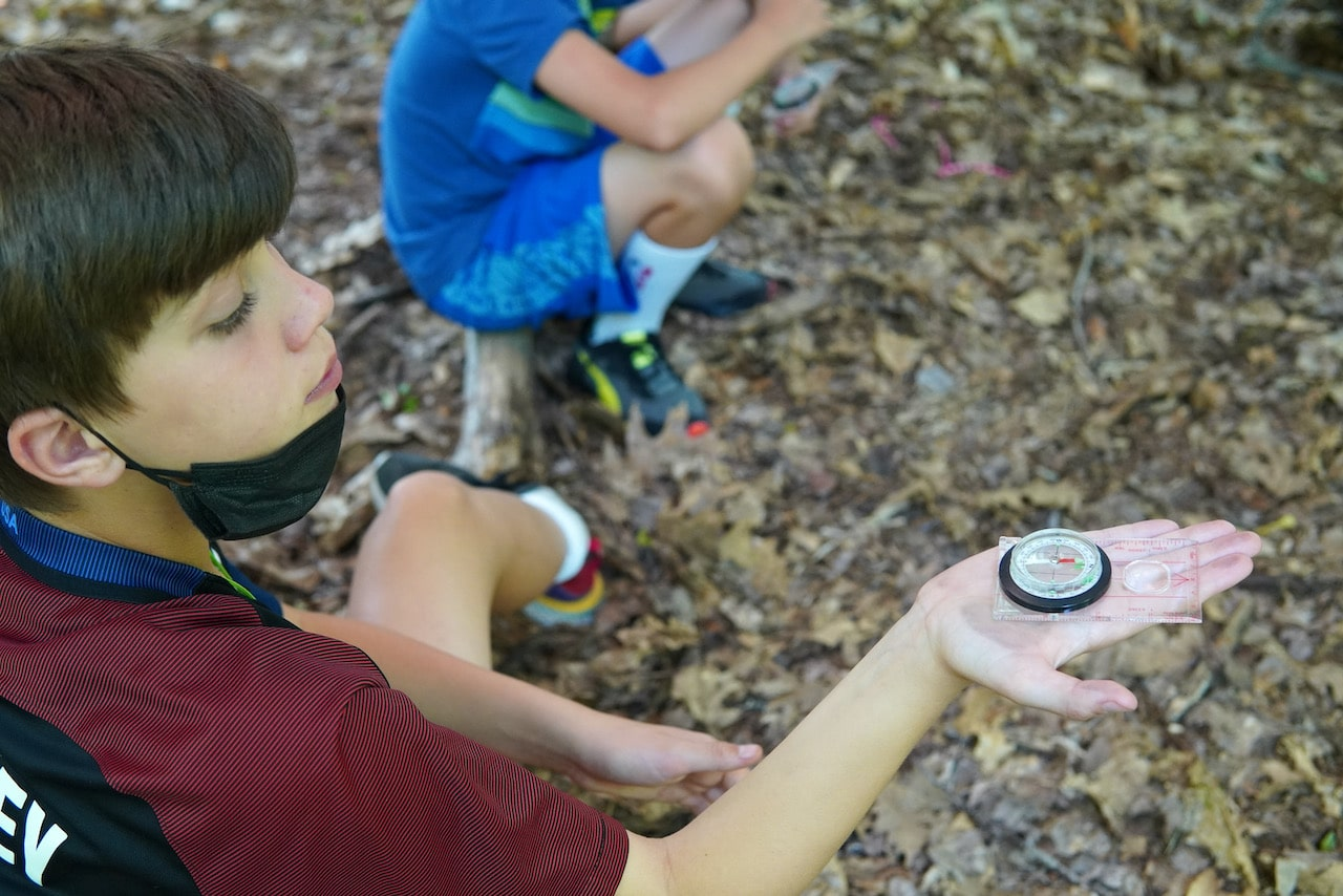 A student holds up his compass while reading the direction