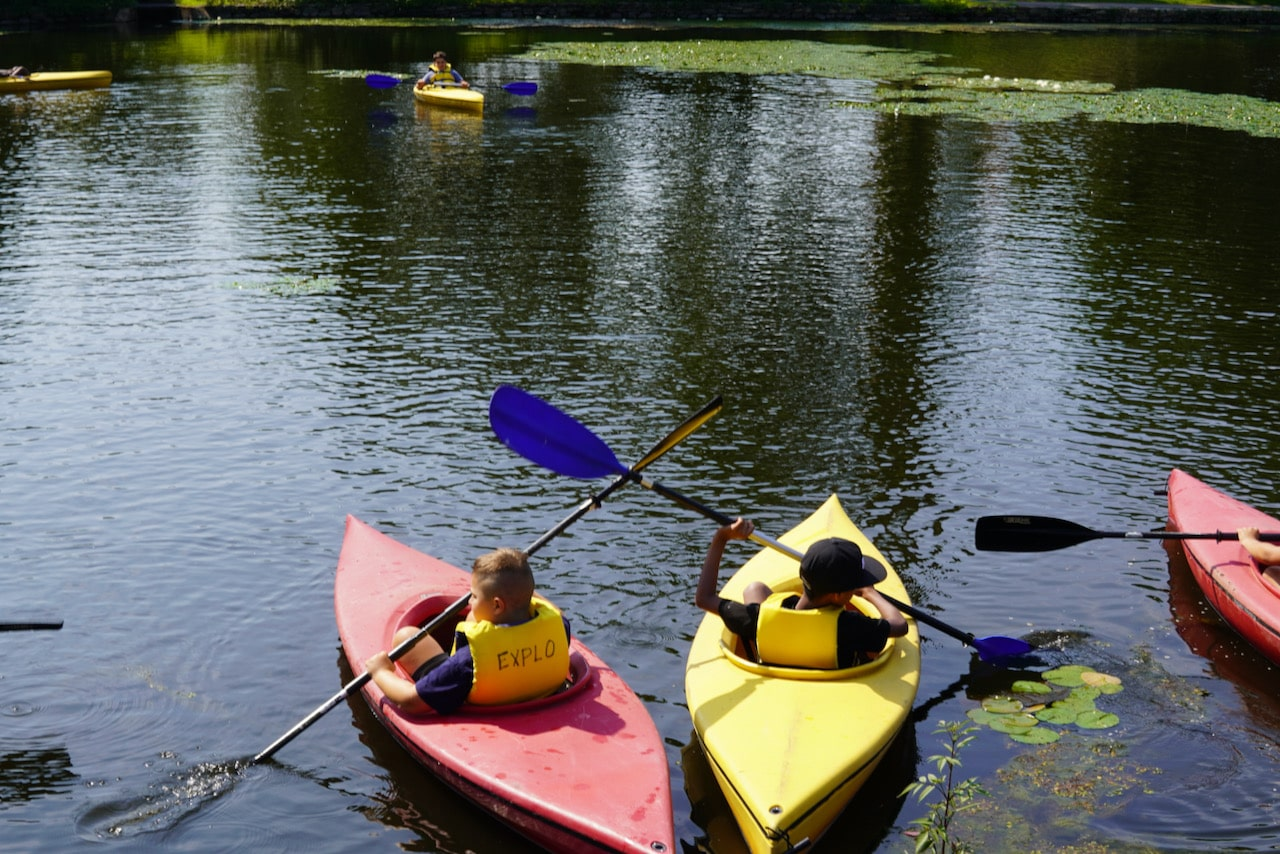 Two students in red and yellow kayaks sit in their boats next to each other