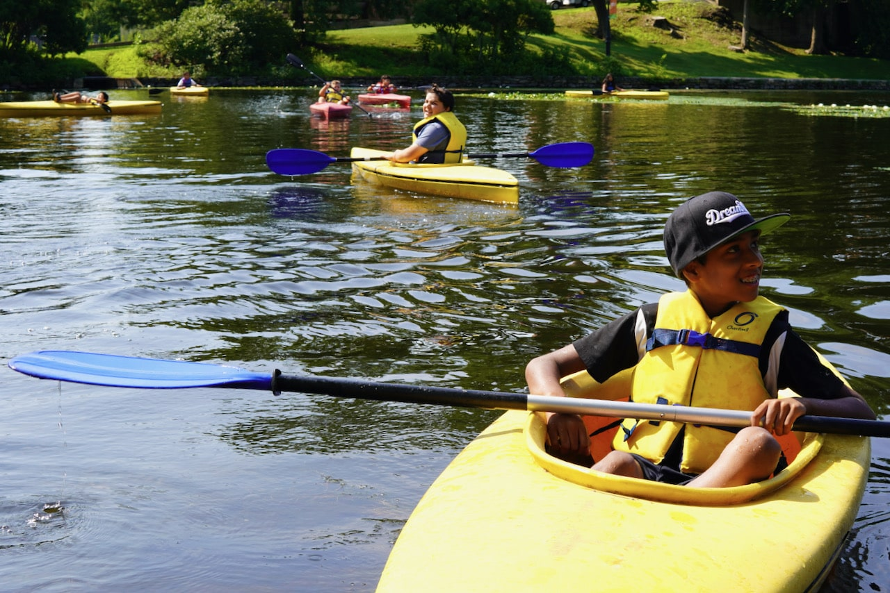 A student smiles while sitting in his yellow kayak