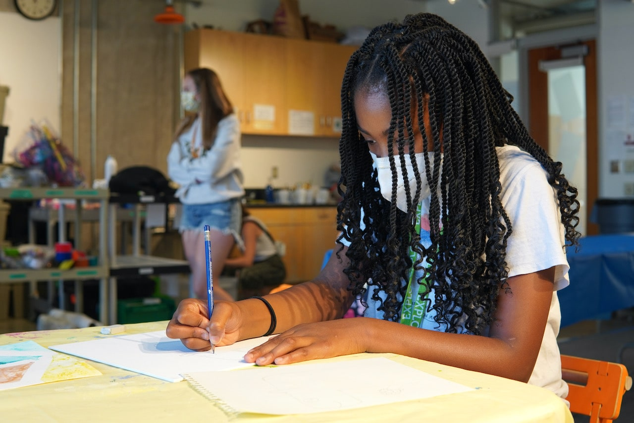 A student uses a pencil to sketch out an idea for a painting
