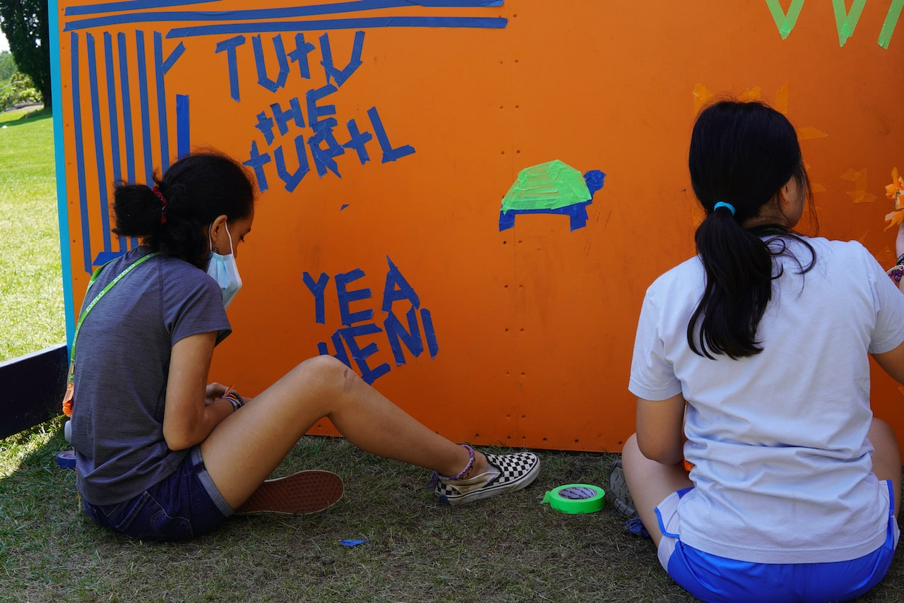 Two students make designs on the wall ball wall with masking tape