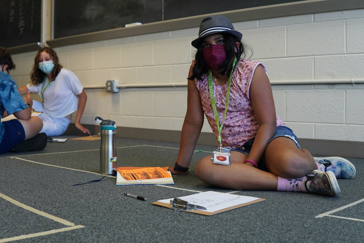 A student sits on the floor while working on her secret language
