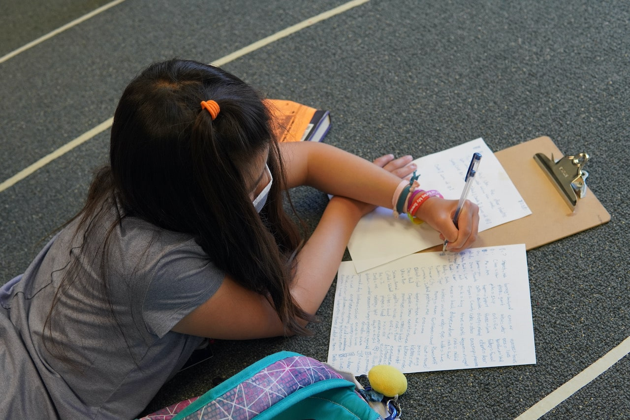 A student lies on the floor while writing out her secret language