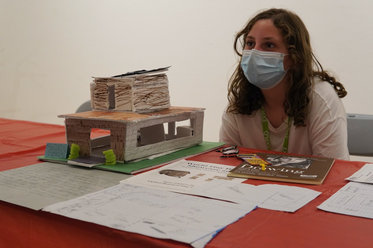 A student sits at a table behind her tiny home model