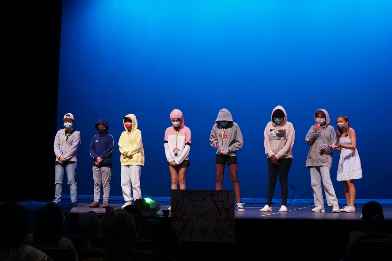 A line of students stand on stage with their hoods up during a singing and dancing performance