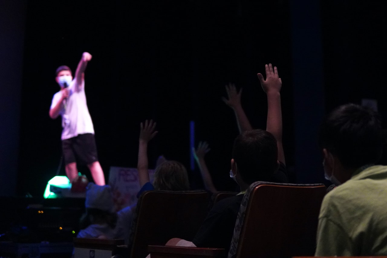 A student points into the crowd to pick a volunteer for his improv performance