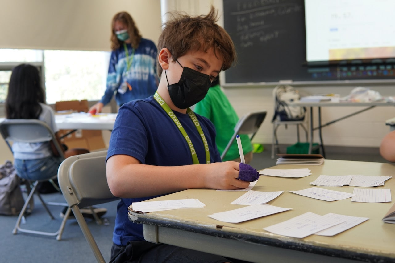 A student concentrates while writing on a notecard at a table