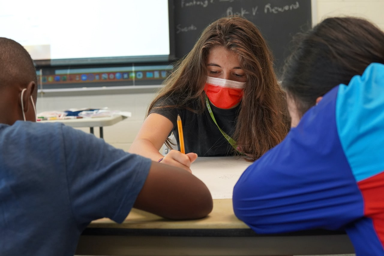 A group of three students work together with two of their backs facing the camera and one student writing with a pencil