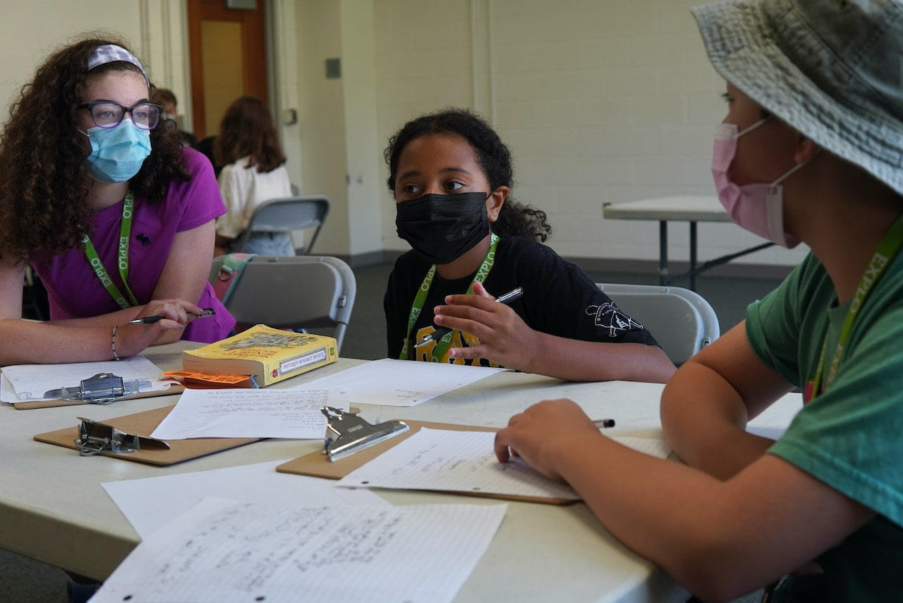 Three students discuss their storyline while taking notes at their table