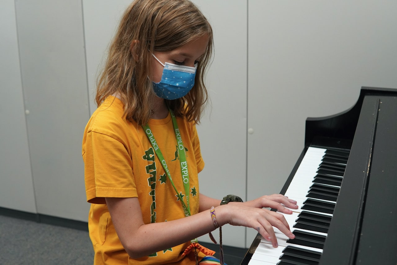 A student plays piano in a piano booth