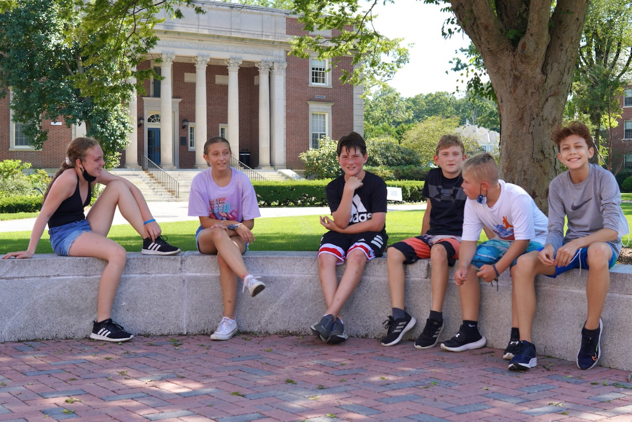 A group of students sit on a bench smiling after finishing the triathlon