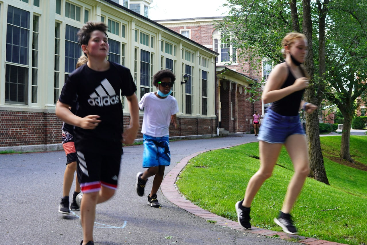 Four students run with each other around the quad